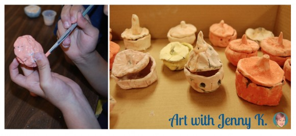 "Decorating clay pumpkin pinch pots from ""10 Halloween Art Lessons for Kids."""